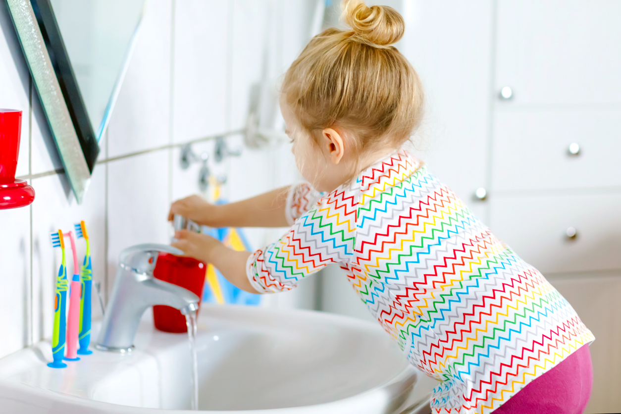 Young toddler washing hands.